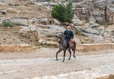 Beduíno que monta um corcel árabe ao longo da estrada que conduz de PETRA - a capital do reino de Nabatean na cidade de Wadi Musa foto de stock
