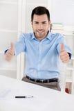 Beduimelt omhoog: Gelukkige trotse zakenmanzitting in zijn bureau het dragen Stock Afbeeldingen