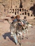 Beduin, das an seinem Esel in PETRA Jordanien sich lehnt Stockbilder
