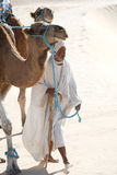 Beduin. Douz, Kebili, Tunisia - September 17, 2012 : Beduins leading tourists on camels at the Sahara desert on September 17, 2012 in Douz, Kebili, Tunisia stock image