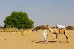 Beduin driver of the camel. THAR DESERT, INDIA - APRIL 01: Beduin driver of the camel all over the Thar desert in Rajasthan, Thar desert in April 01, 2010 royalty free stock photo