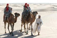 Beduin leading tourists on camels. Douz, Kebili, Tunisia - September 17, 2012 : Beduins leading tourists on camels at the Sahara desert on September 17, 2012 in stock images