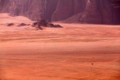 Beduinen, die auf Kamele im Nachtisch fahren Lizenzfreie Stockbilder