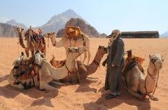 Beduinisch und ihre Kamele Lizenzfreie Stockfotos