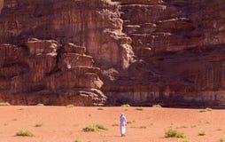 Beduinischer Mann unter enormen Klippen in Wadi Rum-Wüste, Jordanien stockbilder