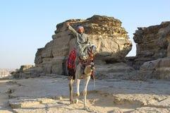Beduino árabe en camello cerca de piedras del desierto Foto de archivo libre de regalías