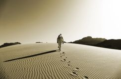 Beduino che cammina sulle dune di sabbia in Wadi Rum Desert, Giordania nel colore di seppia fotografie stock libere da diritti