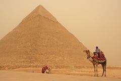 Beduino en un camello cerca de la pirámide de Khafre en un strom de la arena, El Cairo Fotografía de archivo libre de regalías