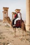 Beduinpojkar som rider kamlet i forntida stad av palmyraen - Syrien Arkivbilder