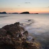 Bedöva landscapedawnsoluppgång med den steniga kustlinjen och lång exp Arkivbilder