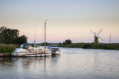 Bedöva landskap av väderkvarnen och floden på gryning på sommarmorni Royaltyfri Bild