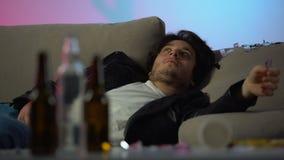 Bedwelmde jonge mensenontwaken op slordige laag na partij, die aan hoofdpijn lijden stock footage