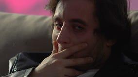 Bedwelmde mens die op bank liggen, die slecht na misbruikte partij, alcohol en drug voelen stock footage
