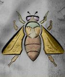 The bee is on colors. Shot in black and white and painted in color detail on the sculpture on the facade of this historic building representing some characters Stock Images