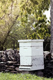 Bee Hive. Beekeepers hive near a rock wall in an apple orchard. Shallow depth of field Royalty Free Stock Image