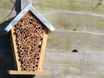 A bee house or hive. A bee hive or home hanging on a fence. effort to encourage nature and help the environment Royalty Free Stock Photos