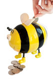 Bee moneybox. Photo of the isolated on white bee moneybox with woman hand inserting coin Stock Images