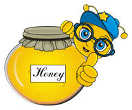 Bee peek up from the bank of honey. Happy bee in blue cap and glasses stick out from the roung closed bank of honey Royalty Free Stock Images
