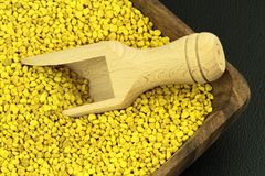Bee pollen. Bee pollen in a wood plate and scoop Royalty Free Stock Image