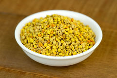 Bee pollen closeup in white bowl on wooden table Stock Image