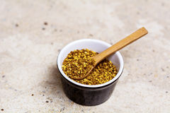 Bee Pollen. In cup  with wooden spoon Royalty Free Stock Photos