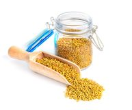 Bee pollen in a glass jar and a wooden shovel is isolated on a white background. Natural remedy for immunity enhancement Royalty Free Stock Photos