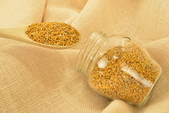 Bee pollen in glass jar and wooden spoon Stock Photo