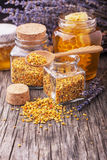 Bee pollen granules and propolis in wooden scoop. Golden bee pollen in small glass jars with honey comb on the texture wooden background with the wooden spoon Stock Image
