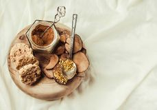Bee pollen in a jar on a wooden stand, Ceylon cinnamon and biscuits, white linen tablecloth background.Copy space.Top view. royalty free stock photos