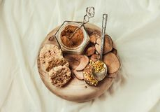 Bee pollen in a jar on a wooden stand, Ceylon cinnamon and biscuits, white linen tablecloth background.Copy space.Top view. royalty free stock images