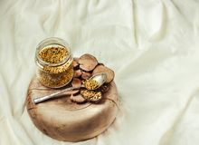 Bee pollen in a jar on a wooden stand, white linen tablecloth.Place for text.Selective focus. royalty free stock photo