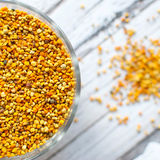Bee pollen. Raw organic bee pollen over wooden board royalty free stock images