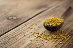 Bee pollen in spoon over wooden background. Healthy organic raw diet vegetarian food ingredient - bee pollen. Beekeeping products. Apitherapy Stock Images