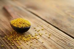 Bee pollen in spoon over wooden background. Healthy organic raw diet vegetarian food ingredient - bee pollen. Apitherapy. Bee pollen in spoon over wooden Stock Photo