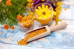 Bee pollen in wooden scoop with yellow flower in plastic glass. On the table royalty free stock image