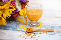 Bee pollen in wooden spoon with glass of liquid pollen behind it. On the table stock photography