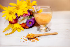 Bee pollen in wooden spoon and glass with liquid pollen. On the table royalty free stock photo