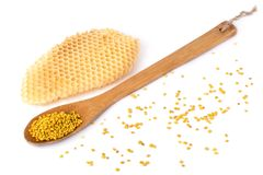 Bee pollen in a wooden spoon and a honeycomb on white background. Beekeeping products. Apitherapy. Bee pollen in a wooden spoon and a honeycomb on white royalty free stock photo