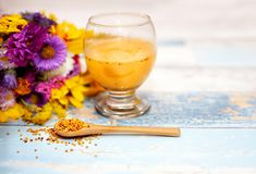 Bee pollen in wooden spoon with pollen liquid in the glass. With flower in the background royalty free stock image