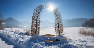 Beech arch at lakeside promenade schliersee with bench. Bavarian winter landscape Royalty Free Stock Image