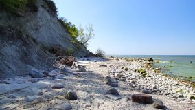 Beach in Wolin National Park in Western Poland. Stones and rocks on the beach. High and steep cliff. Photo taken during sunny may day in 2009. Photo in 16:9 Stock Images