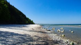 Beech in Wolin National Park in Western Poland. Stones and rocks on beach. High and steep cliff. Shadow of trees on beach. Photo taken during sunny may day in Stock Photo