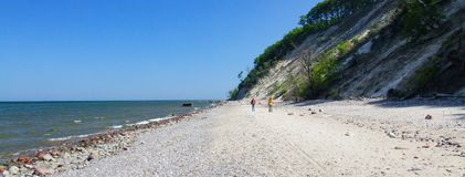 Beach in Wolin National Park in Western Poland. Two people walking. Stones and rocks on a beach. High and steep cliff. Photo taken during sunny may day in 2009 Royalty Free Stock Photos