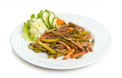 Beef. Juicy fried chopped beef with a pickled cucumbers and vegetable side dish. Isolated on white. Isolated by clipping path Royalty Free Stock Image