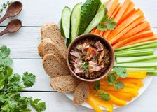 Beef bacon liver pate with raw vegetables. Fresh homemade beef bacon liver pate in ceramic bowl served with raw vegetables on white rustic background Royalty Free Stock Images