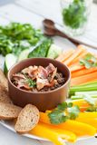 Beef bacon liver pate with raw vegetables. Fresh homemade beef bacon liver pate in ceramic bowl served with raw vegetables on white rustic background Stock Photos