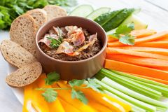 Beef bacon liver pate with raw vegetables. Fresh homemade beef bacon liver pate in ceramic bowl served with raw vegetables on white rustic background Stock Image