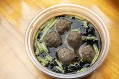 Beef ball clear soup with vegetables and seaweed chinese style in plastic bowl on wooden table of restaurant of Chaozhou. Beef ball clear soup with vegetables royalty free stock photos