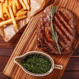 Beef barbecue ribeye steak with chimichurri sauce and french fri. Es, top view Royalty Free Stock Photos