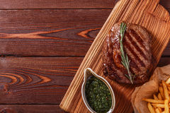 Beef barbecue ribeye steak with chimichurri sauce and french fri. Es, top view Royalty Free Stock Image